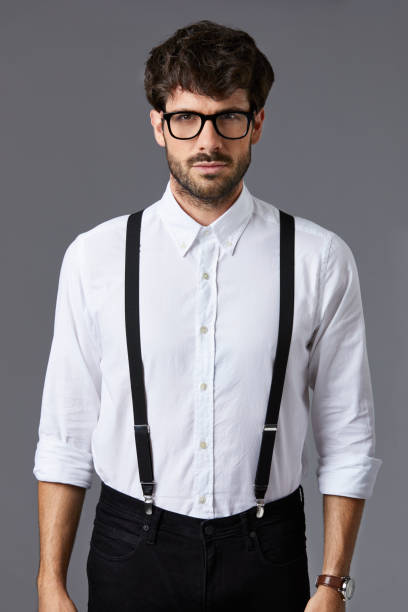 Confident businessman against gray background Portrait of confident businessman standing against gray background. Handsome male professional is in white shirt and suspenders. Creative executive is wearing eyeglasses. suspenders stock pictures, royalty-free photos & images