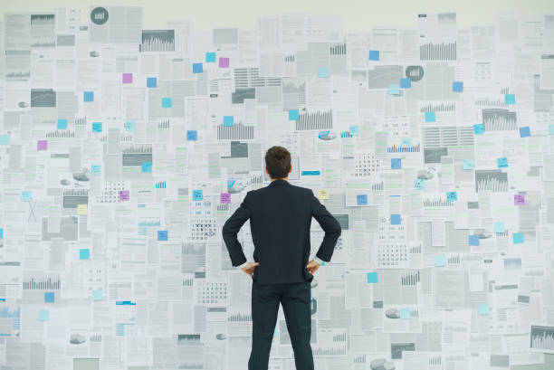 Confident businessman analyzing financial charts Corporate businessman standing with arms akimbo in front of a wall with lots of financial reports, business strategies and planning concept akimbo stock pictures, royalty-free photos & images