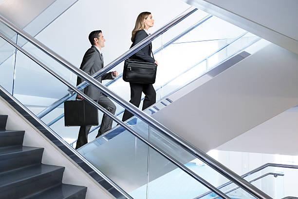 Confiante Empresário e Empresária caminhando até lance de escadas - foto de acervo