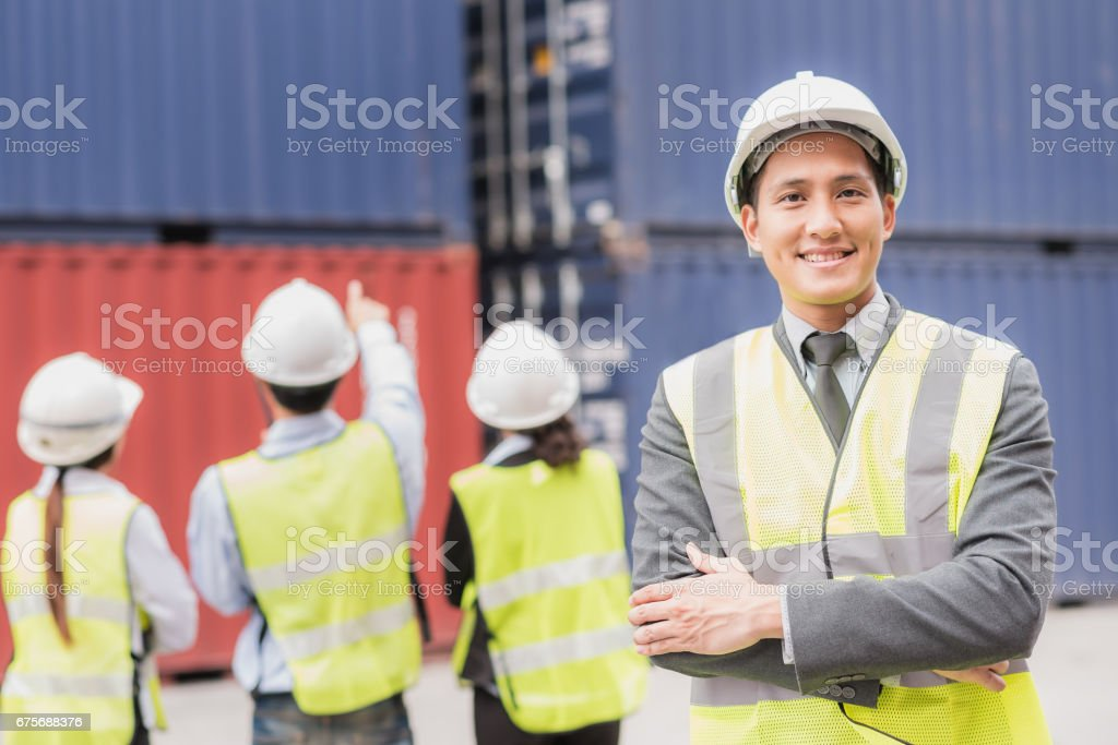 Confident businessman and team with shipping cargo container freight in background. stock photo