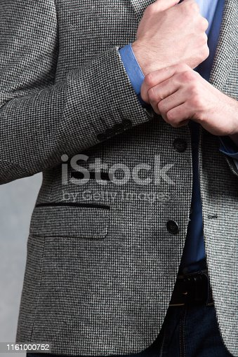 istock Confident businessman. Cropped shot of businessman in stylish suit straightens the sleeve. 1161000752