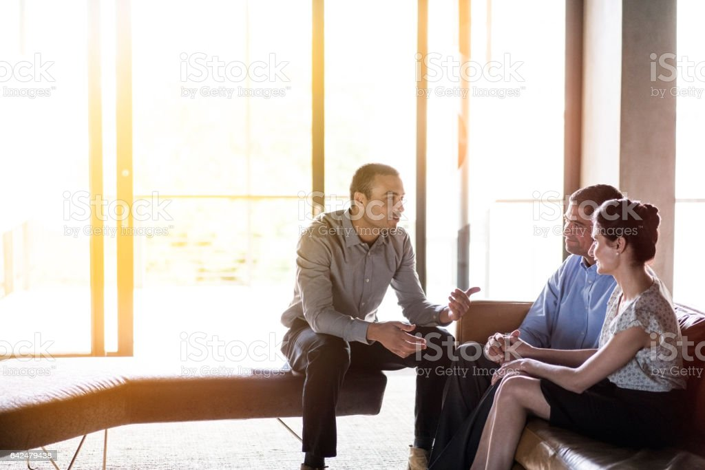 Confident businessman discussing with couple stock photo
