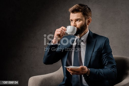 1081599130 istock photo confident businessman drinking coffee and holding saucer 1081599134
