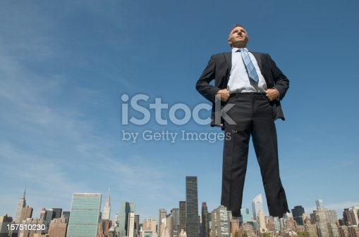 Confident smiling tall businessman giant standing with his hands on his hips, towering over the city skyline