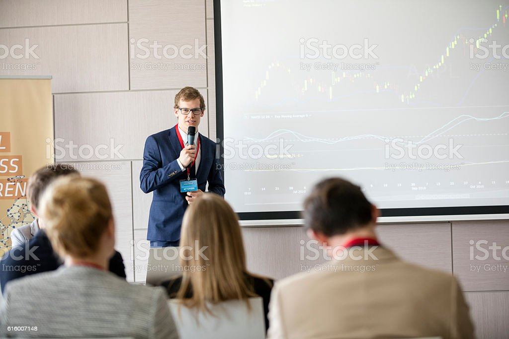Confident businessman giving presentation in seminar hall at convention center stock photo