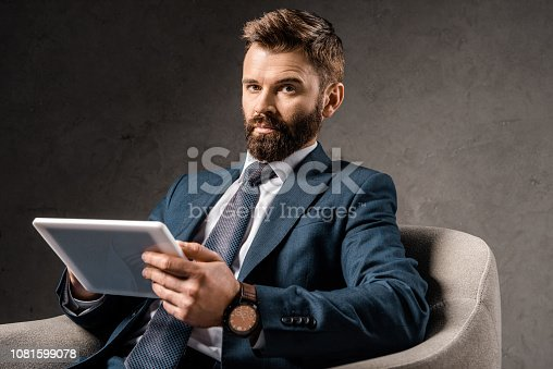 1081599130 istock photo confident businessman holding digital tablet and sitting in armchair 1081599078