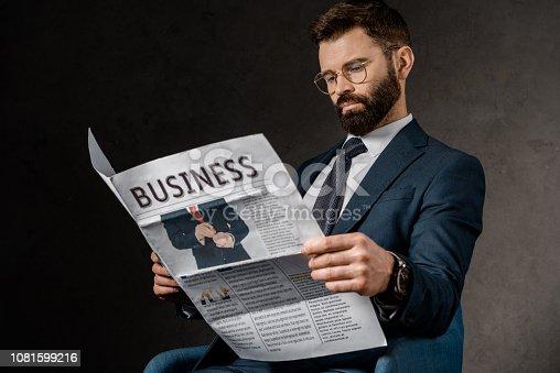 1081599130 istock photo confident businessman in formalwear reading newspaper 1081599216