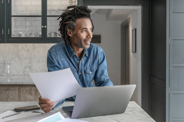 Confident businessman in his 50s working from home with laptop and paperwork stock photo