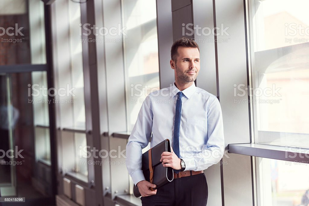 Confident businessman in office, holding a briefcase Portrait of confident businessman wearing shirt and tie standing by the window in an office, holding a leather briefcase in hands. 2015 Stock Photo