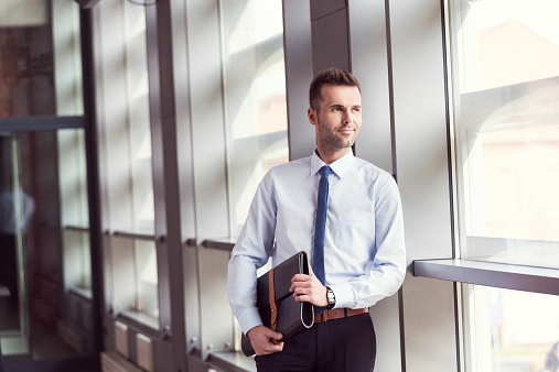 Confident Businessman In Office Holding A Briefcase Stock Photo - Download Image Now