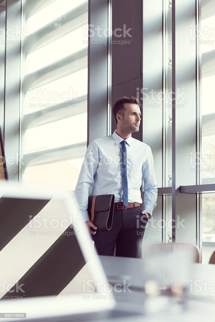 Confident businessman in office, holding a briefcase Portrait of confident businessman wearing shirt and tie standing by the window in an office, holding a leather briefcase in hand. 2015 Stock Photo