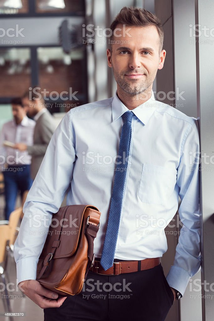 Confident businessman in the office, holding a briefcase Portrait of confident businessman wearing shirt and tie standing by the window in the conference room, holding a brown leather briefcase and smiling at the camera. Blured coworkers in the background. 2015 Stock Photo
