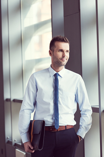 Confident Businessman In The Office Holding A Briefcase Stock Photo - Download Image Now