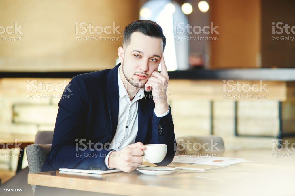 Confident businessman in white shirt and jacket sitting at table in cafe, drinking coffee and thinking royalty-free stock photo