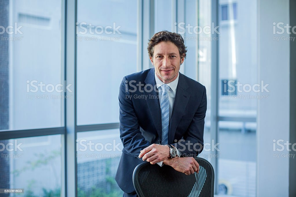 Confident businessman leaning on chair stock photo