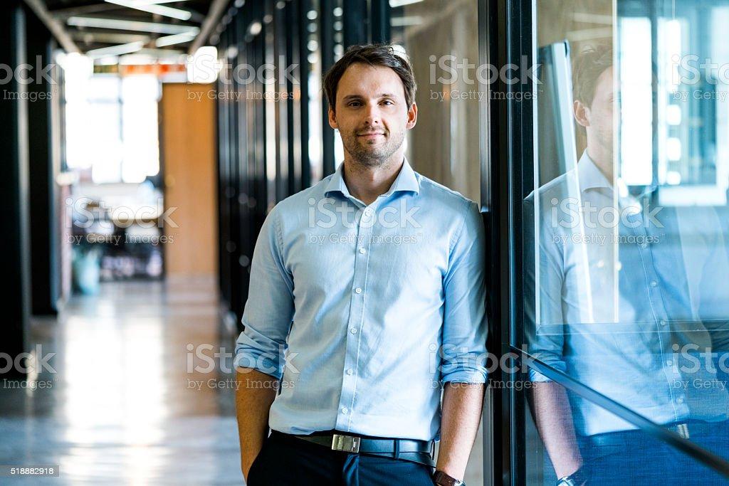 Zuversichtlich Geschäftsmann Gegen eine Wand im Büro Lizenzfreies stock-foto