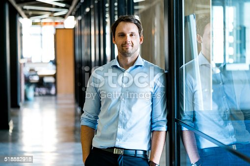 A photo of confident mid adult businessman standing with hands in pockets. Male executive is leaning on glass wall. He is in formals at office.