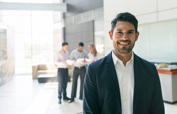 Confident businessman looking at camera very happy while other business people work at the background stock photo