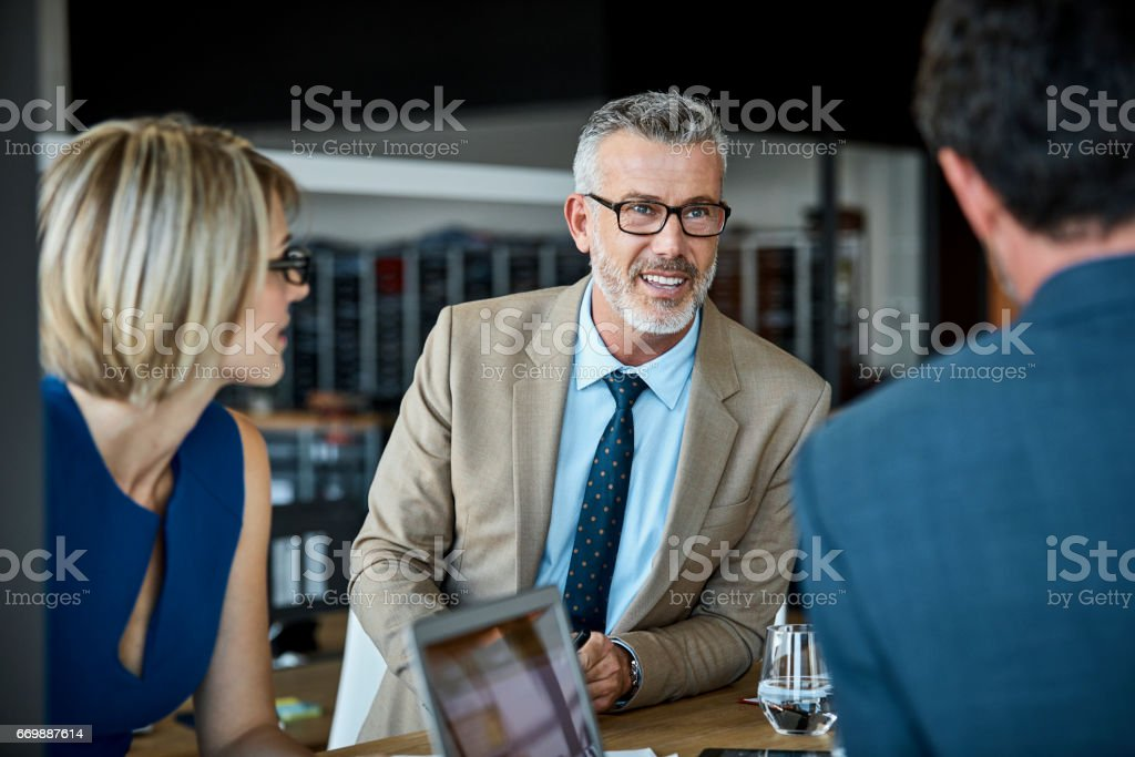 Confident businessman looking at colleague stock photo