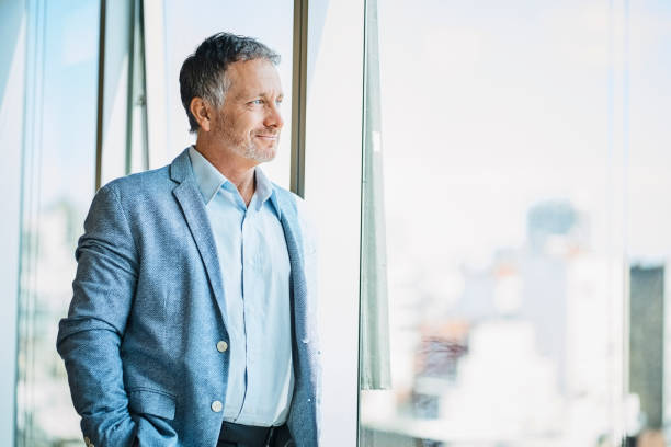 Confident businessman looking through window stock photo