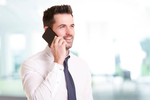 Zuversiger Geschäftsmann, der einen Anruf macht, während er im Büro steht – Foto