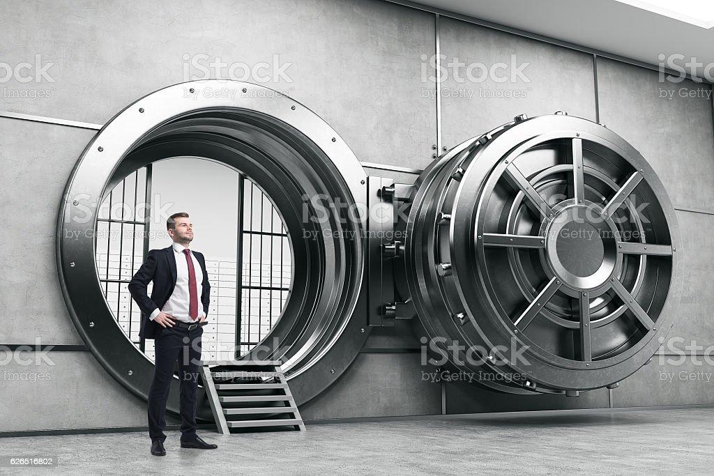 Confident businessman near open vault door stock photo