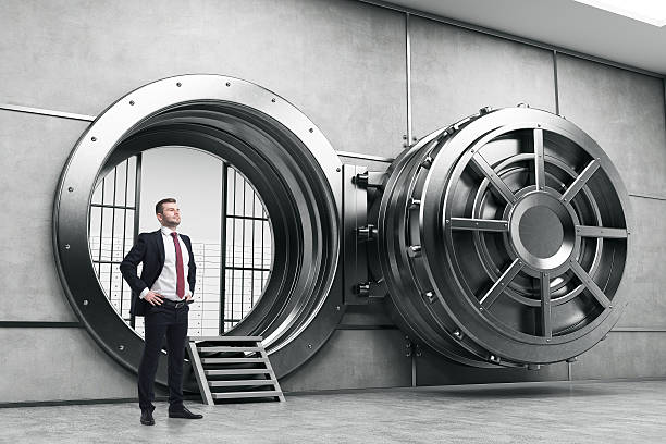 confident businessman near open vault door - bankgeheimnis stock-fotos und bilder