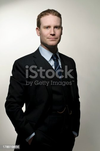 Confident businessman on a grey background.  This photo shows a man in a tailored three piece suit with pocket watch and chain.  This image is of a real man (non model) with no makeup or professional re-touching.