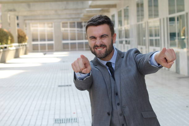 confident businessman pointing at camera - arrogance stock pictures, royalty-free photos & images