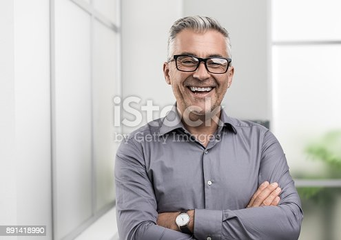istock Confident businessman posing in the office 891418990