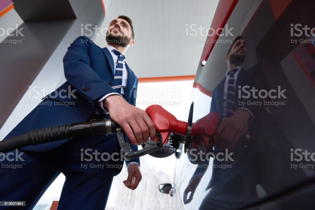 Confident Businessman Refueling car at Gas Station stock photo
