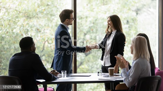 509032417 istock photo Confident businessman shake hand greeting female colleague 1212172530