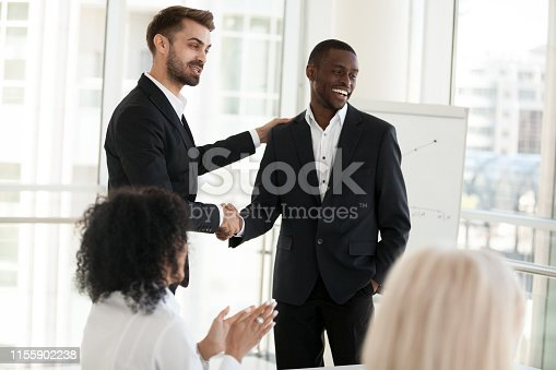 924520168 istock photo Confident businessman shaking hand of African American business partner 1155902238