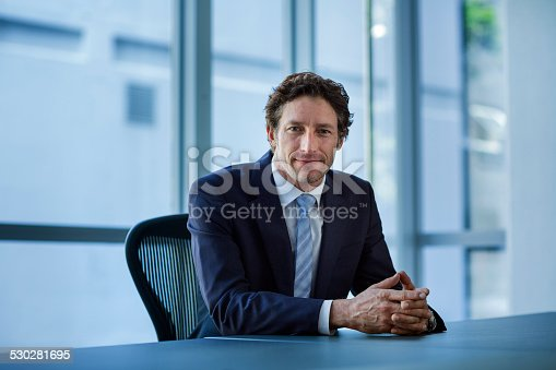Portrait of confident businessman sitting at conference table in office