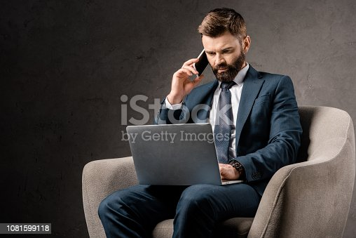 1081599130 istock photo confident businessman sitting in armchair with laptop and talking on smartphone 1081599118