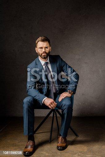 1081599130 istock photo confident businessman sitting in formalwear on chair 1081599208