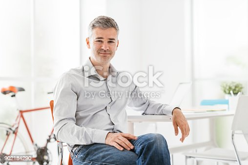 istock Confident businessman sitting in his office 902184290