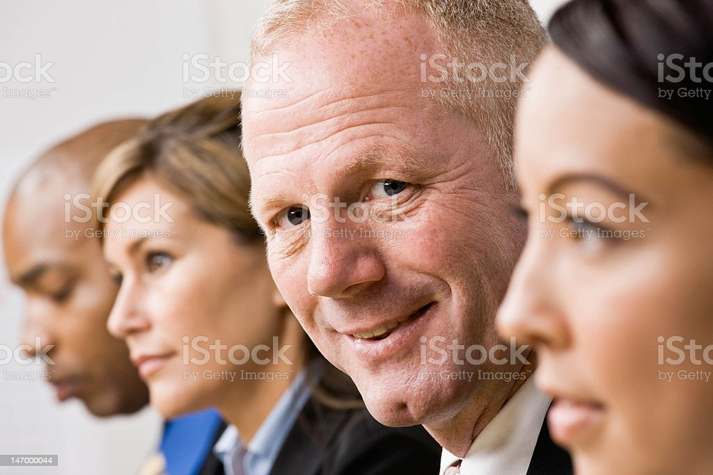 Confident businessman sitting with co-workers royalty-free stock photo