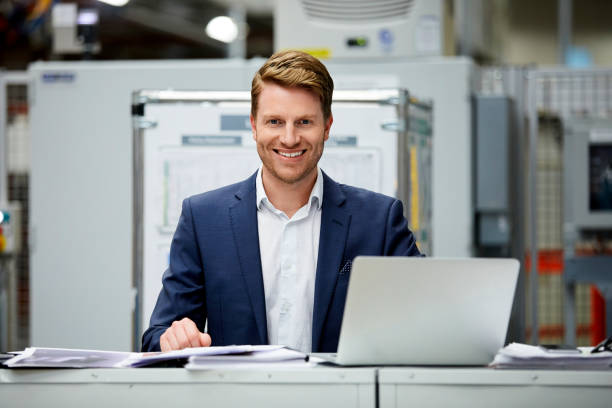 Confident businessman sitting with laptop at desk stock photo