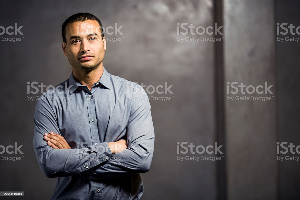 Confident businessman standing arms crossed stock photo