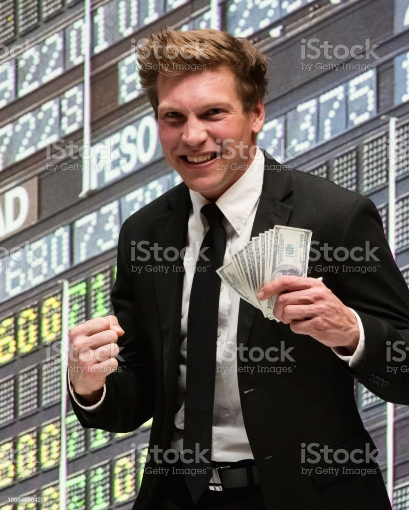 Confident businessman standing at the stock market and holding money in his hand stock photo