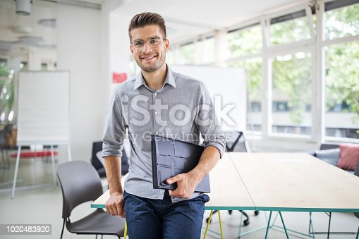 Portrait of handsome young businessman standing by conference table in new office. Confident man with file looking at camera and smiling.