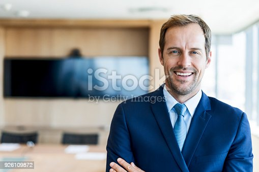 Portrait of confident mid adult businessman in board room. Business professional is standing in office. Male is smiling at workplace.