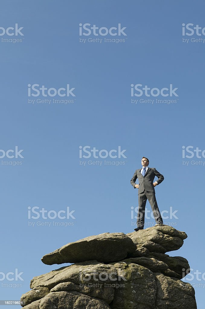 Confident Businessman Standing Tall on Mountain Peak royalty-free stock photo
