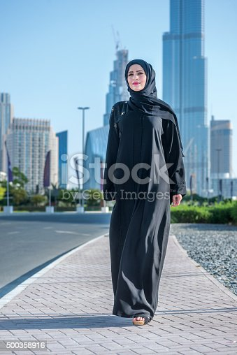 Confident businessman sweeping the Arab Dubai. Arab Business vumen hijab is in the streets against the skyscrapers of Dubai. The woman is dressed in a black abaya