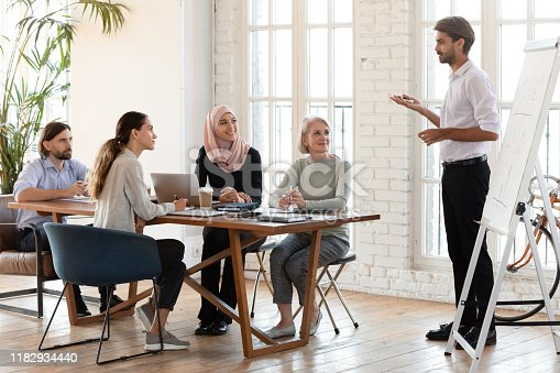 1031235468 istock photo Confident businessman trainer give flip chart presentation at corporate training 1182934440