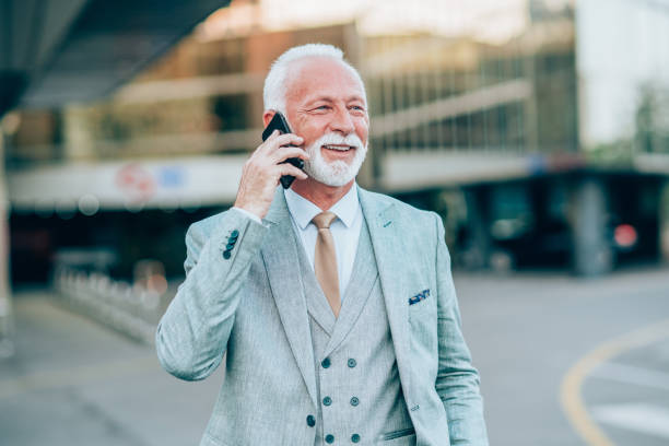 confident businessman using cellphone on city street - violetastoimenova stock photos and pictures