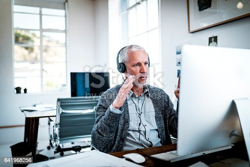 istock Confident businessman video conferencing at desk 641968256