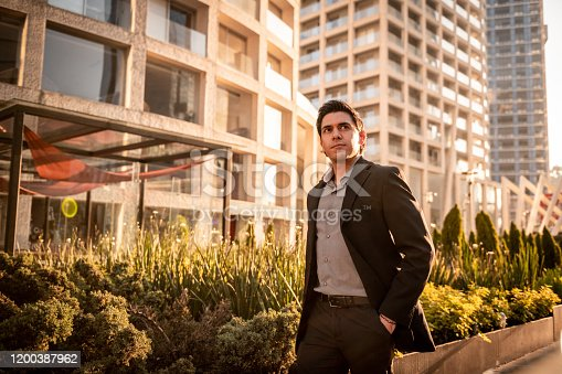 Confident businessman walking down the city street