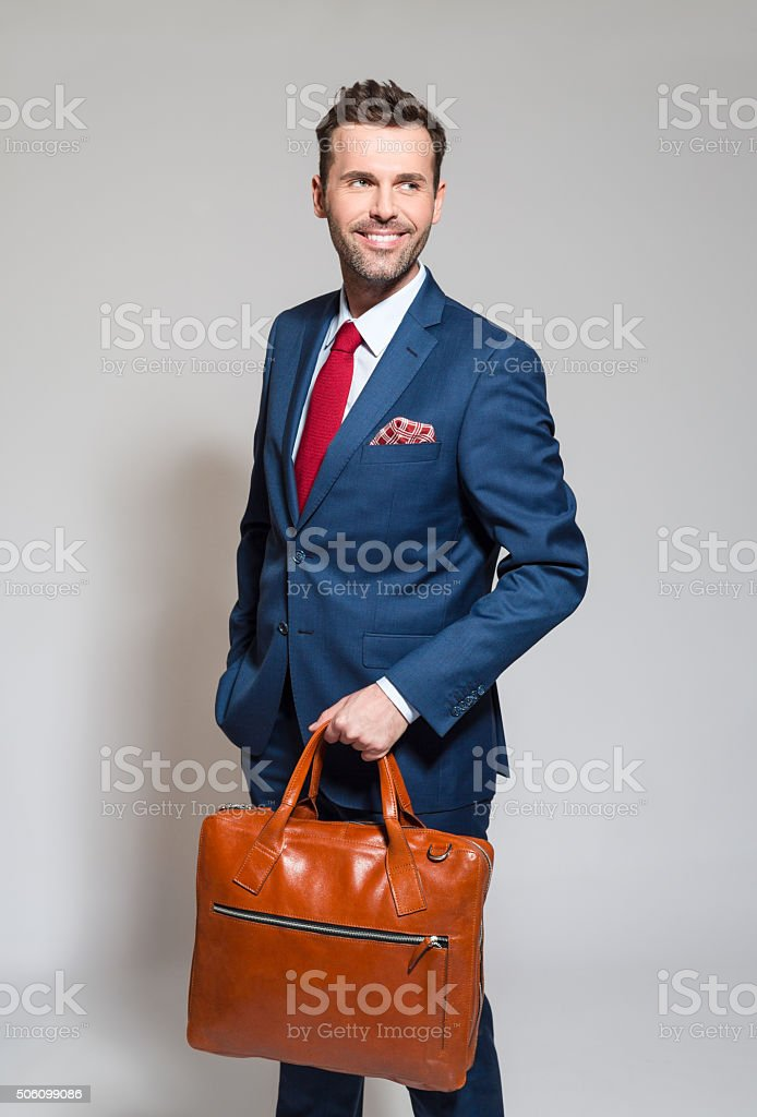 Confident businessman wearing elegant suit, holding briefcase Portrait of elegant businessman wearing elegant suit, holding a leather briefcase in hand. Studio shot, one person, grey background. Adult Stock Photo